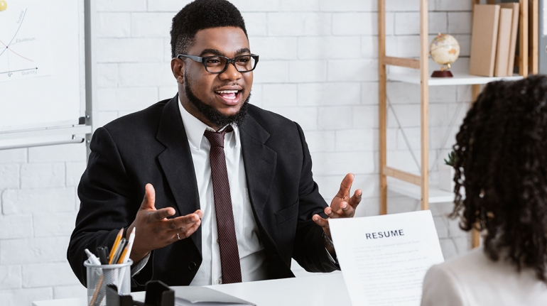 Human resources manager communicating with positive vacancy applicant on employment interview at office. HR specialist talking to job candidate, looking through CV